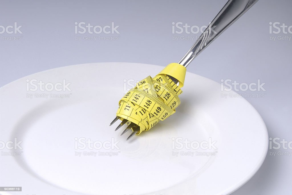 Measuring Tape Wrapped Around Fork on a Plate royalty-free stock photo