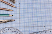 Measuring tools above  blue graph paper.