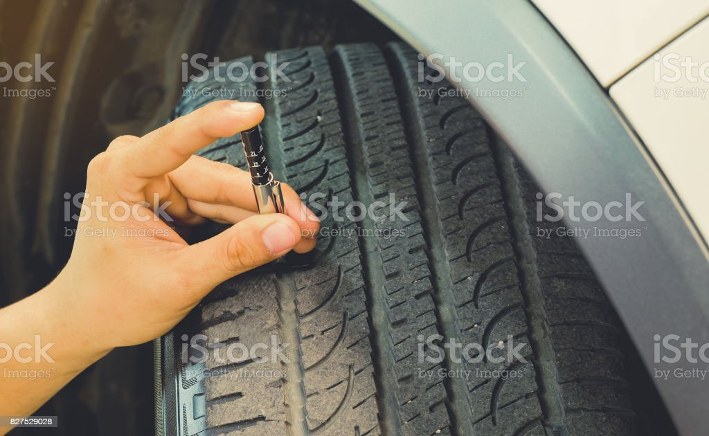 Measuring tread wear on a tire on a car.Safe to use on a daily basis. stock photo