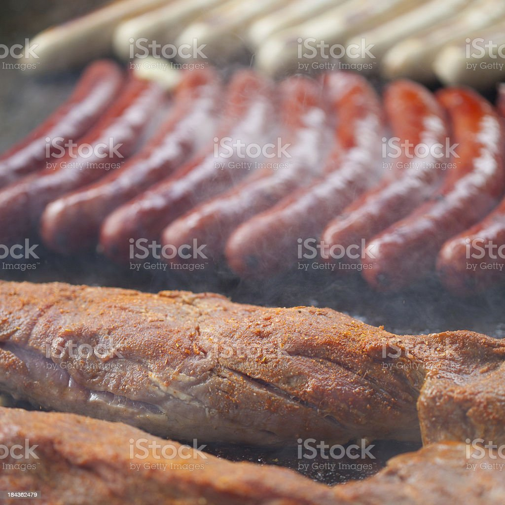 Meat and German sausages on barbecue grill royalty-free stock photo