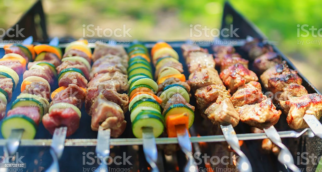 Meat and vegetable skewers on grill in nature stock photo