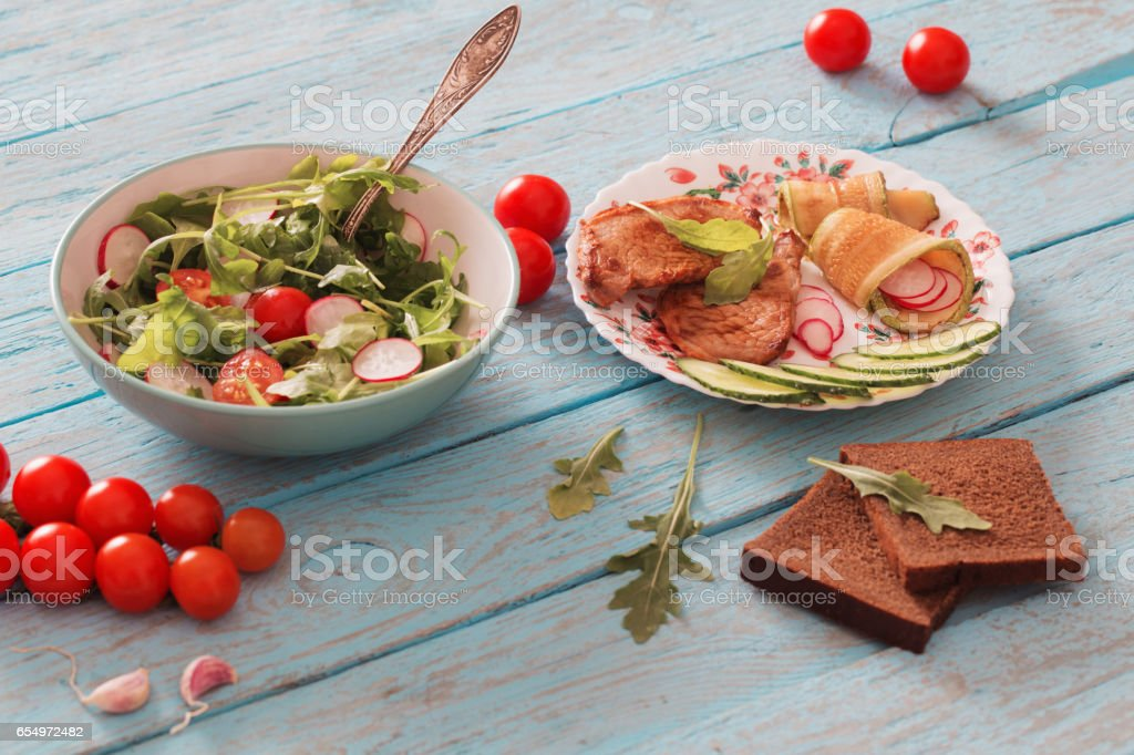 meat and vegetables on old wooden table stock photo
