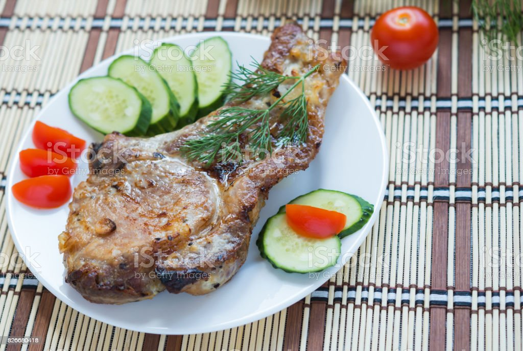 Meat and Vegetables. Roasted Pork with cucumbers and tomatoes. Ribeye Steak stock photo