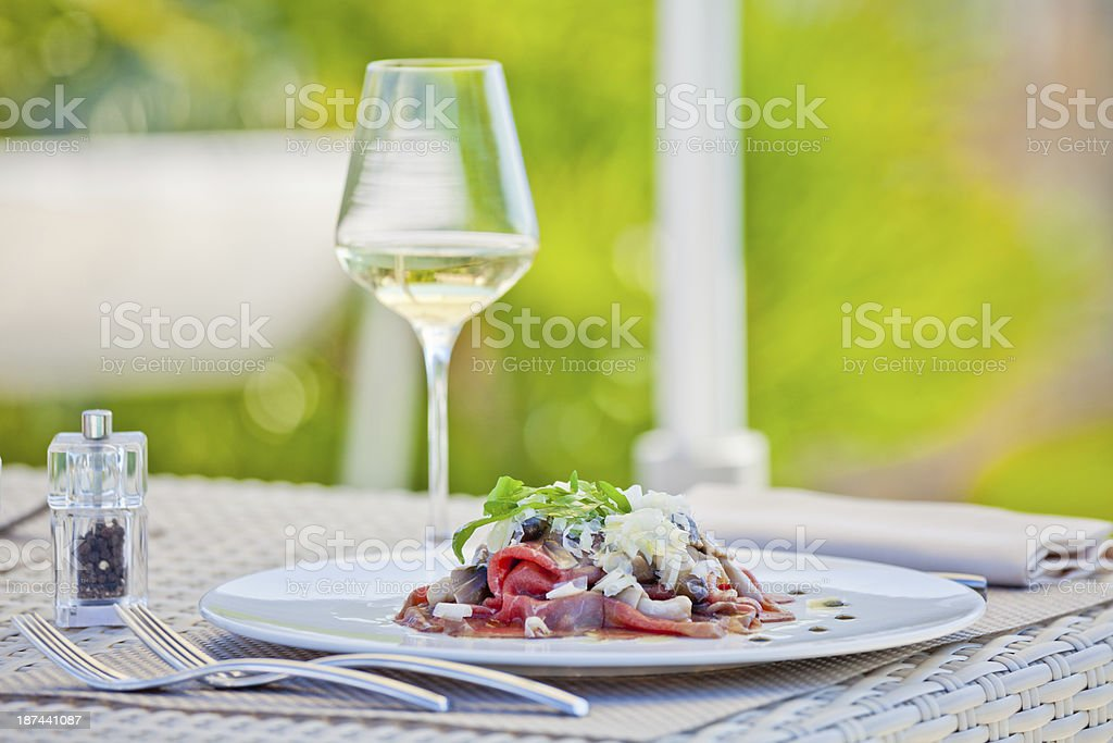 Meat and White Wine in Restaurant at Summer royalty-free stock photo