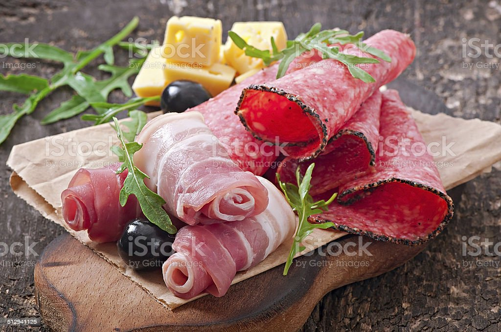 Meat appetizer on old wooden background stock photo
