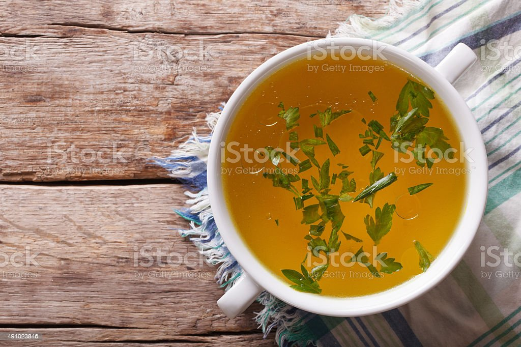 meat broth with parsley in bowl closeup. horizontal top view stock photo