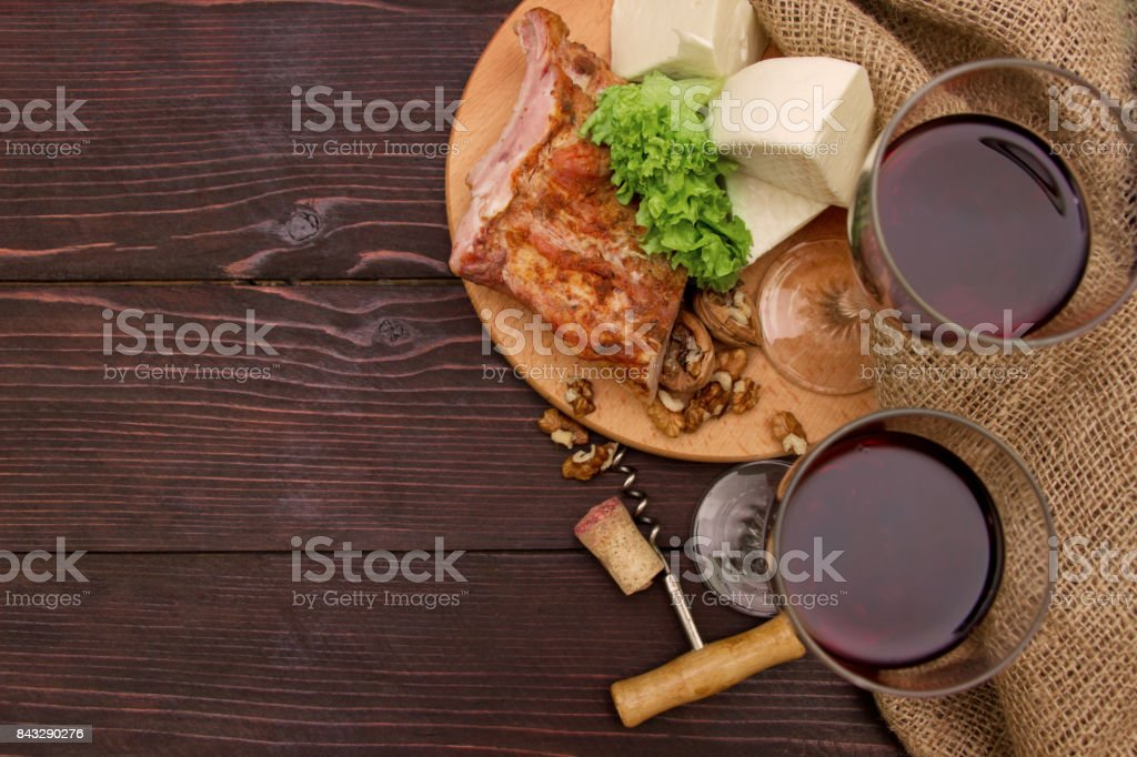Meat, cheese and wine glasses on a table with linen cloth on background of wooden planks stock photo