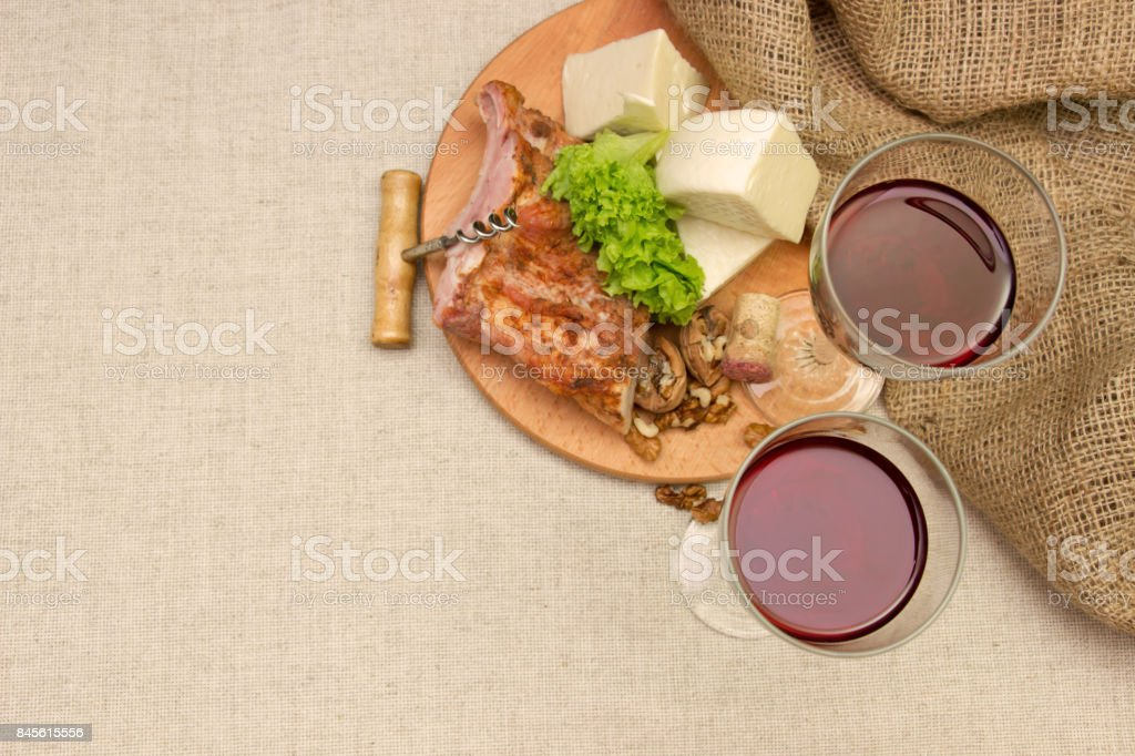 Meat, cheese and wine glasses on a table with linen cloth stock photo