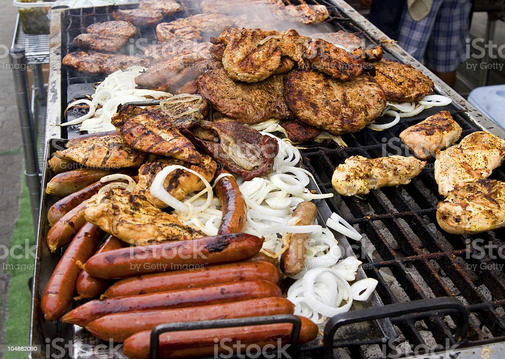 Meat cooking on a vendors grill stock photo