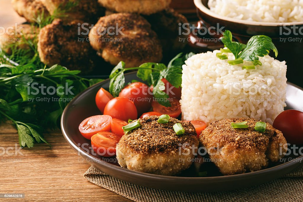 Meat cutlets with boiled rice and tomatoes on wooden background. stock photo