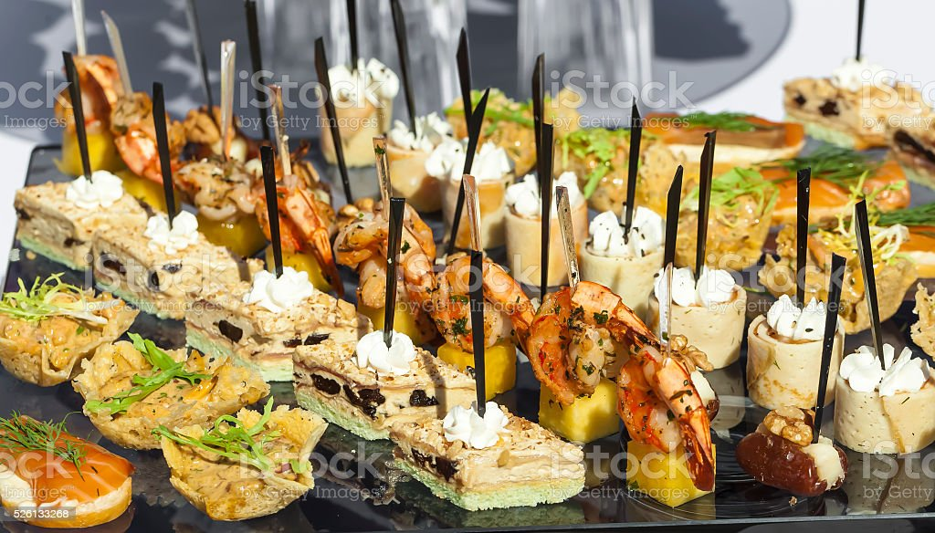 meat, fish, vegetable canapes on a festive wedding table outdoor stock photo