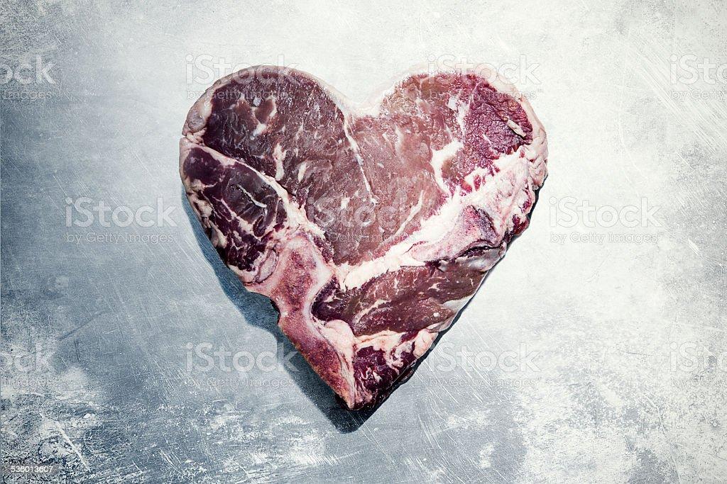 A raw T-bone steak in the shape of a heart on a worn stainless steel...