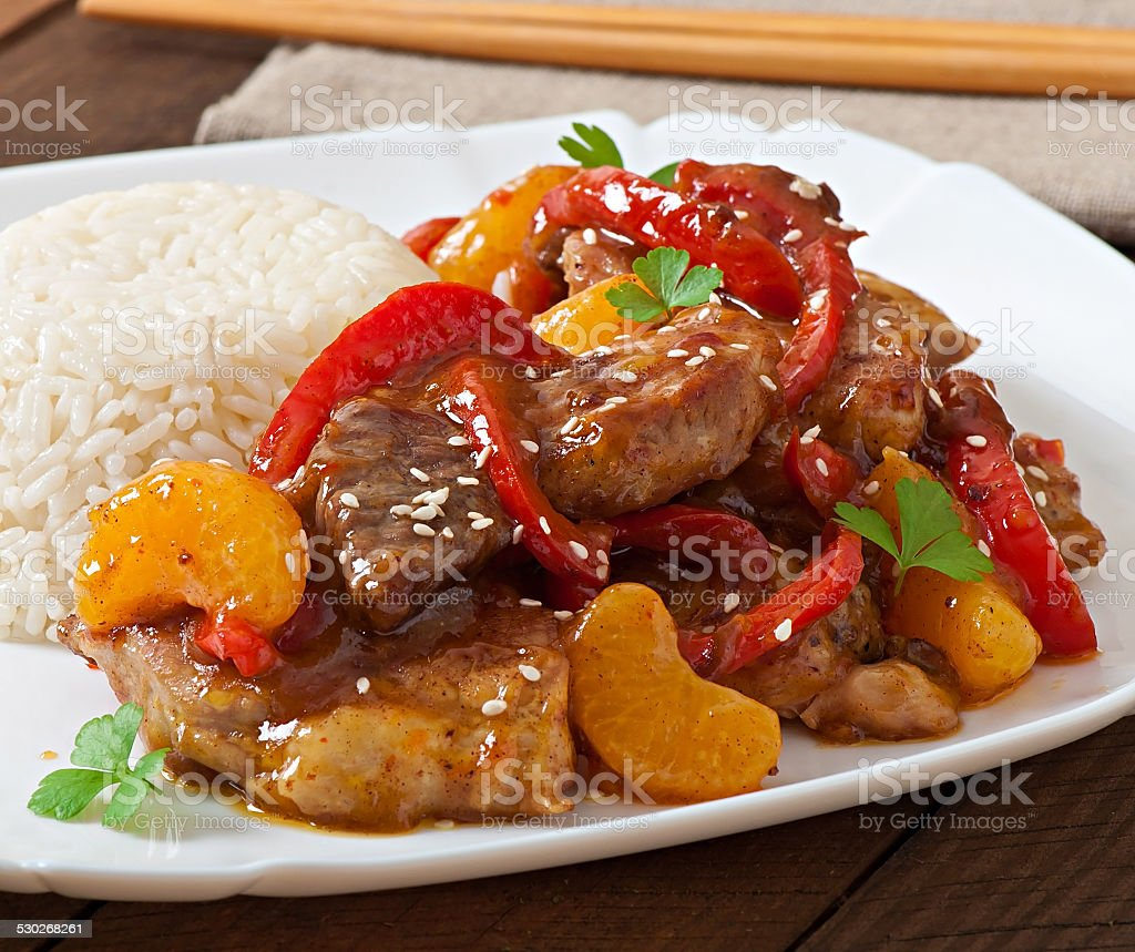 Meat in a spicy sauce, sweet pepper and tangerines stock photo