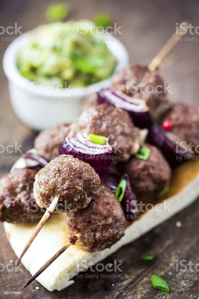 Meat kebab, beef balls on skewer with onions, sauce guacamole stock photo