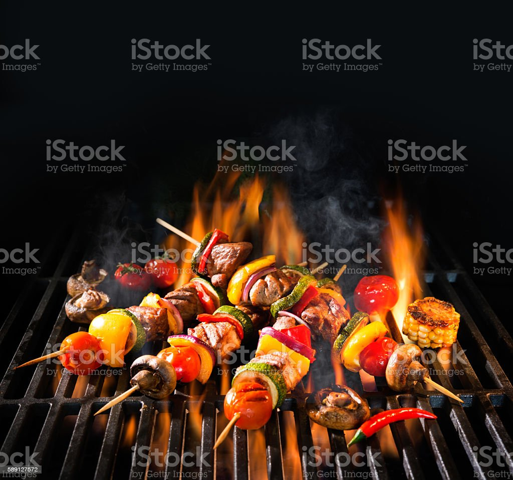 Meat kebabs with vegetables on flaming grill stock photo