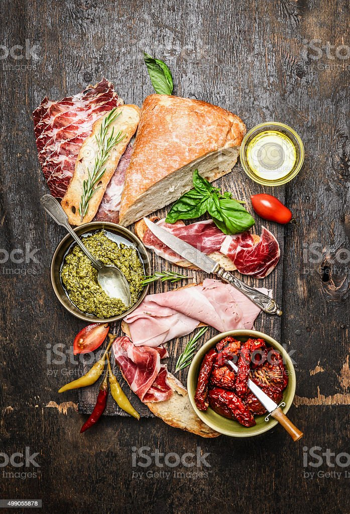 Meat plate with various antipasti, ciabatta bread, pesto and ham stock photo