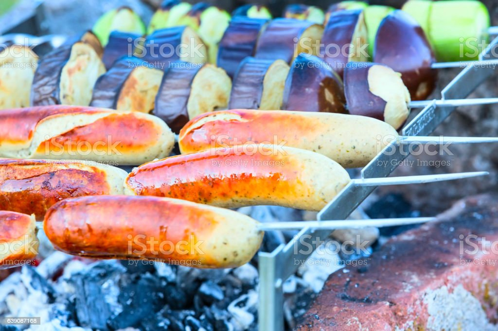 Meat sausage and grilled vegetables cooked on coals stock photo