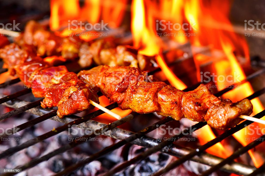 meat skewers in a barbecue stock photo