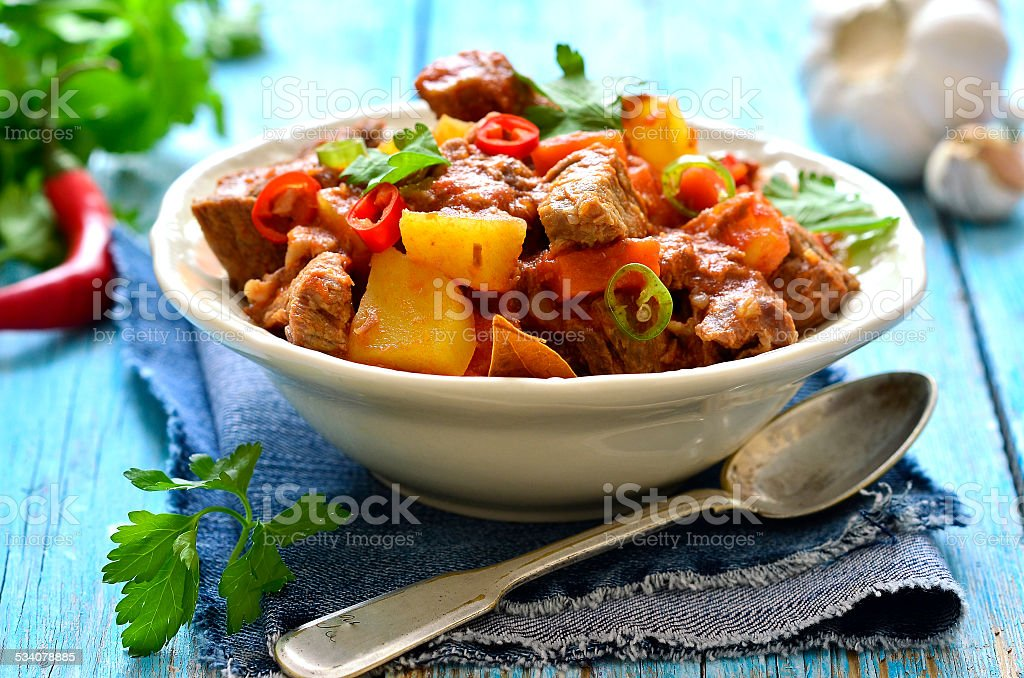 Meat stewed with vegetable in spicy tomato sauce. stock photo