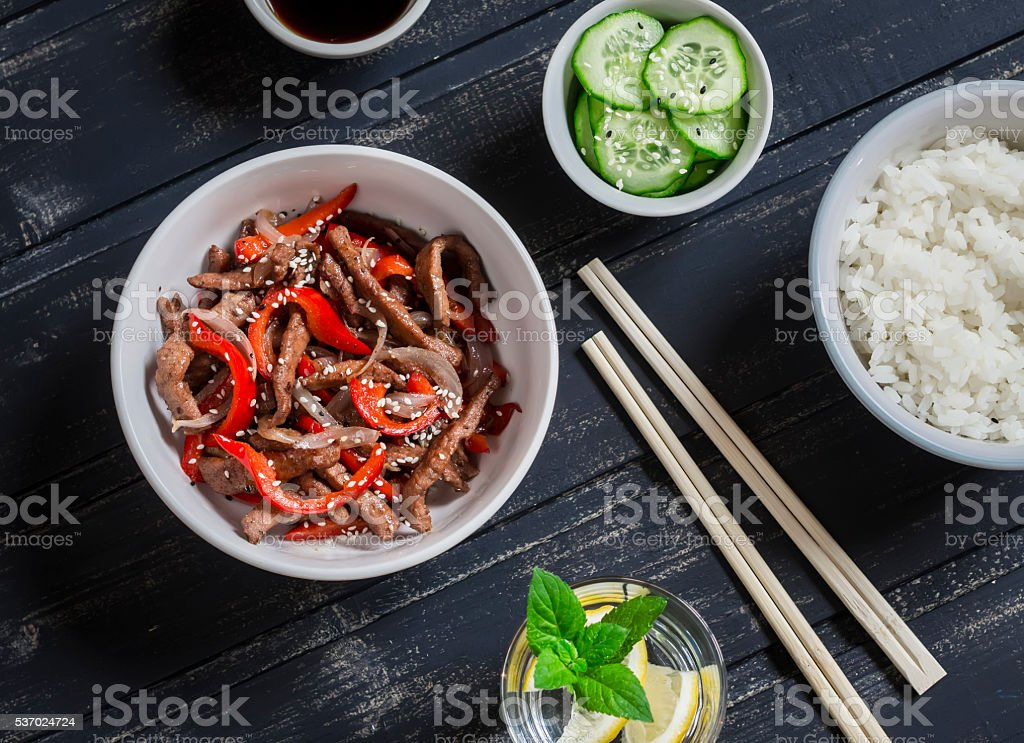 Meat stir fry with pepper, rice and fresh cucumber stock photo