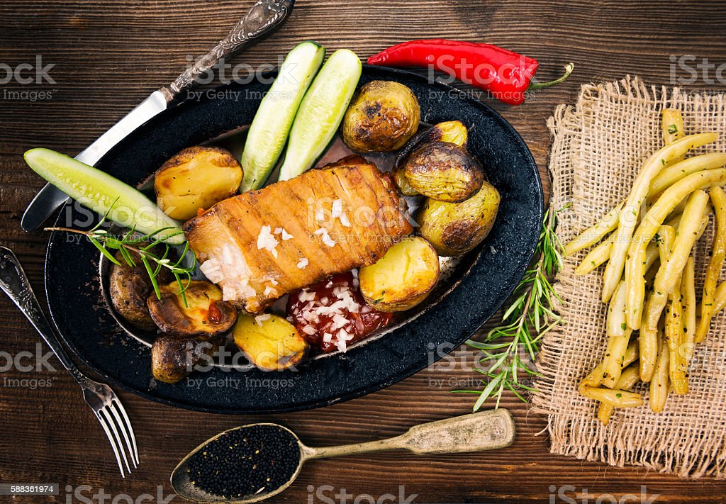 Meat with fried potatoes on wooden table stock photo