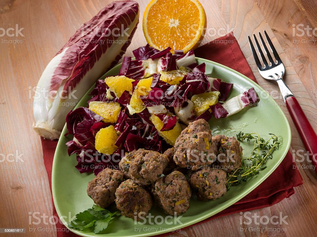 meatball with red chicory and orange salad stock photo