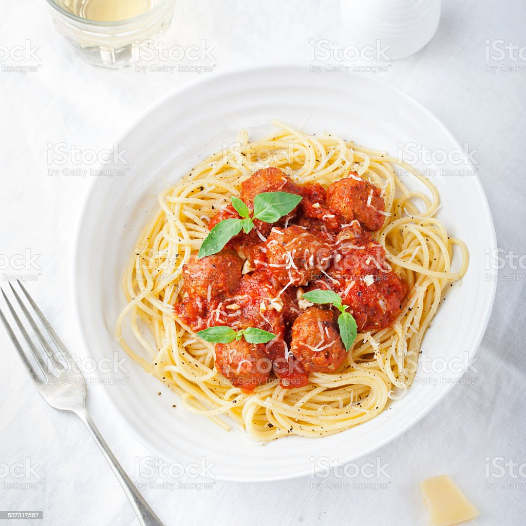 Meatballs in tomato sauce and fresh basil with spaghetti stock photo