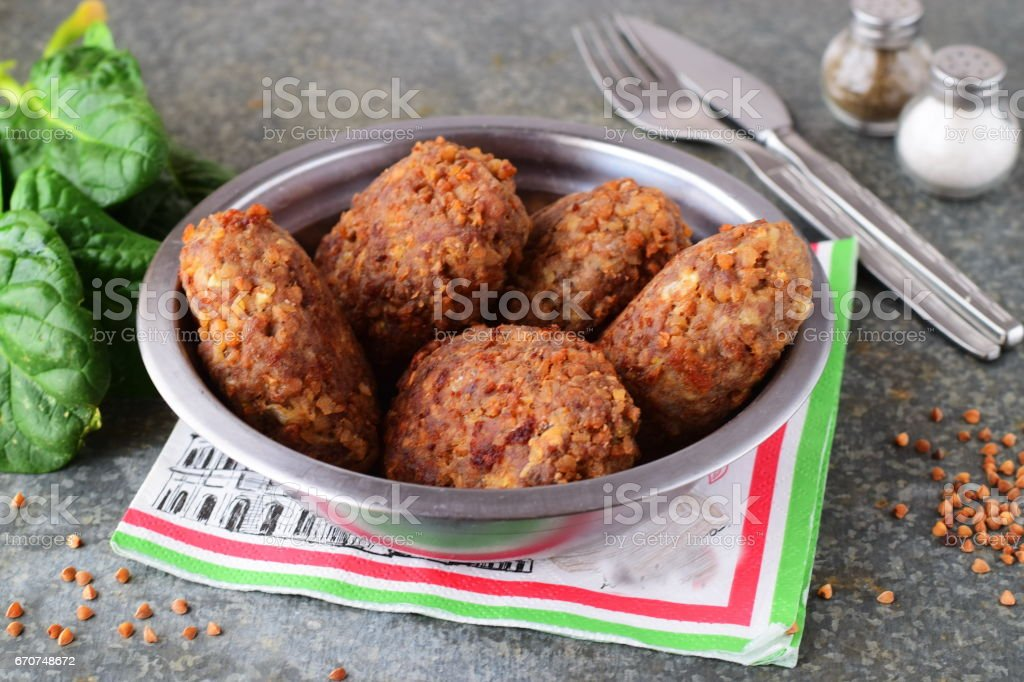Meatballs with buckwheat in a metal bowl on a grey abstract background.Healthy food.Healthy eating concept. stock photo