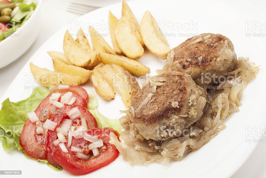Meatballs with stewed onion and fried potato wedges stock photo