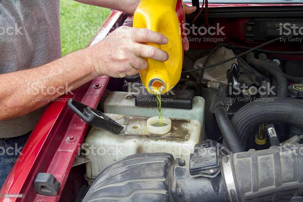 Mechanic Adding Coolant To A Older Truck stock photo