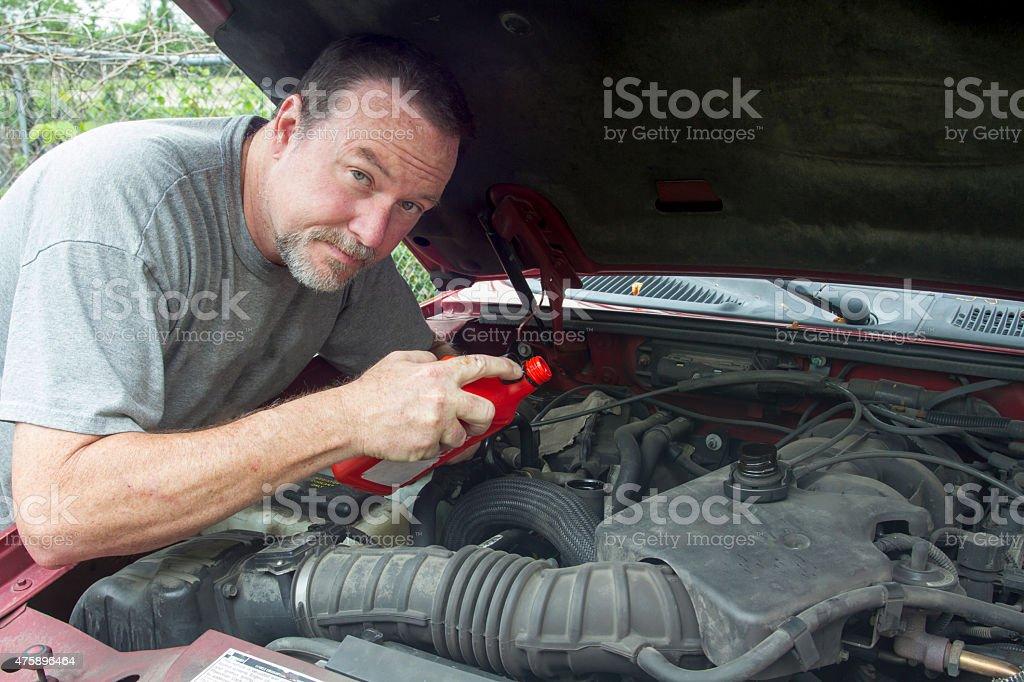 Mechanic Adding Oil To Older Truck stock photo