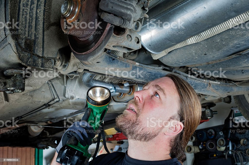 Mechanic At Work Checking Brake Assembly stock photo
