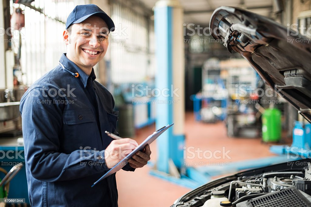 Mechanic at work in his garage stock photo