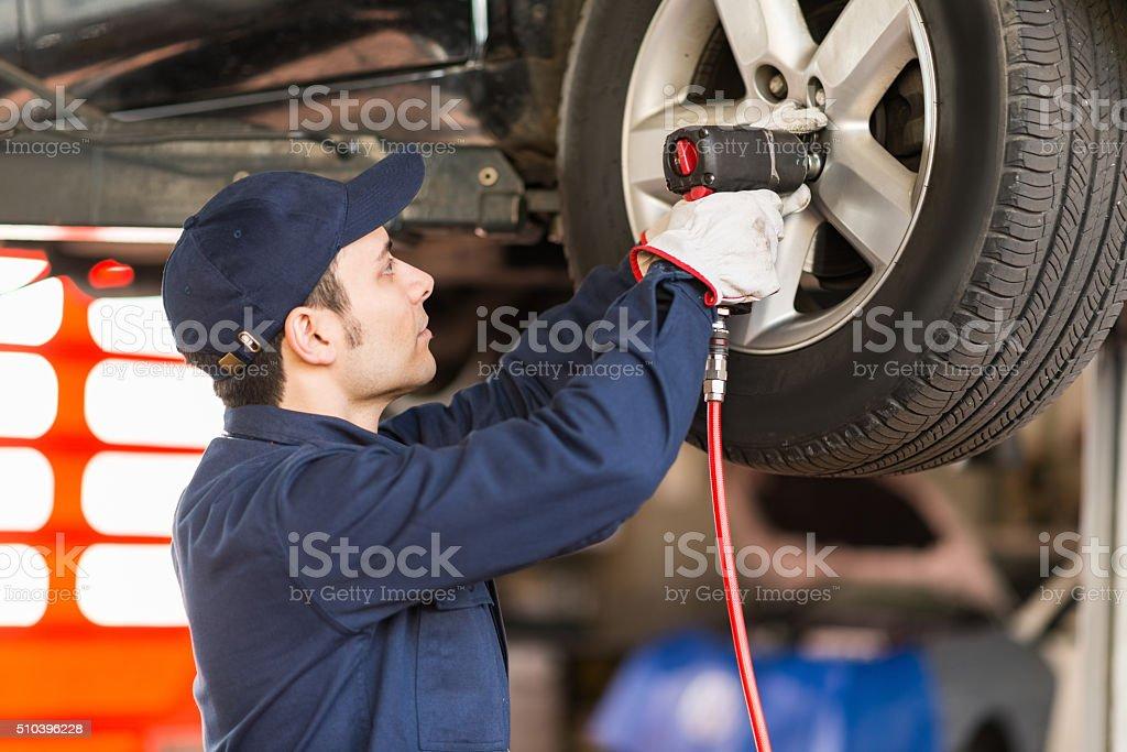 Mechanic at work in his garage stock photo