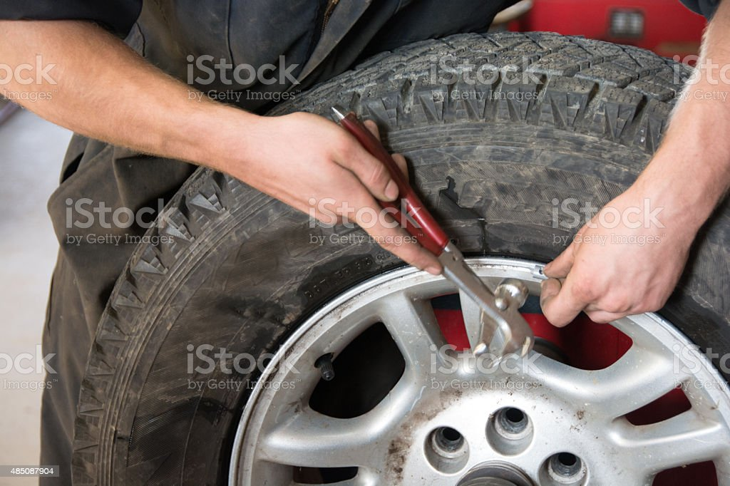 Mechanic balancing a truck tire with weights stock photo