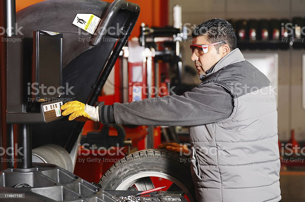Mechanic balancing tire in car shop royalty-free stock photo