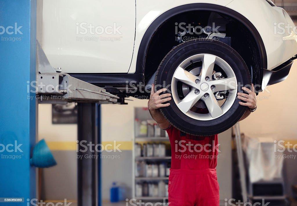mechanic behind tire stock photo