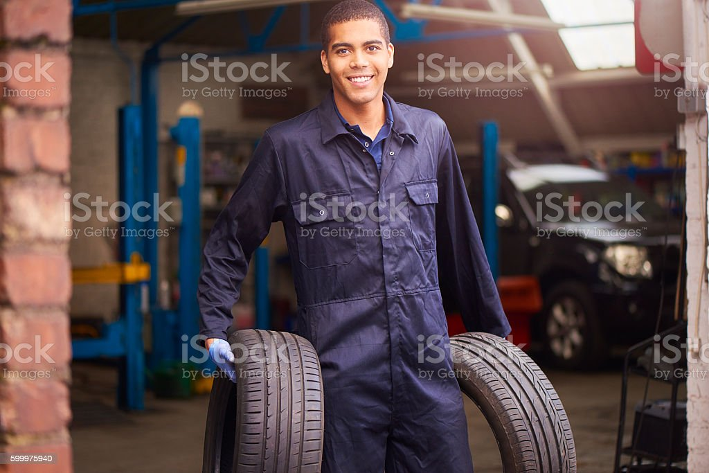 Mechanic carrying two tyres stock photo