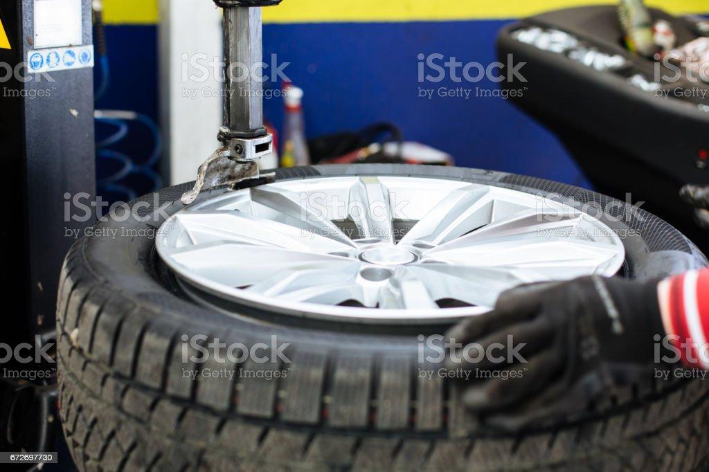 Mechanic changing a car tire closeup stock photo