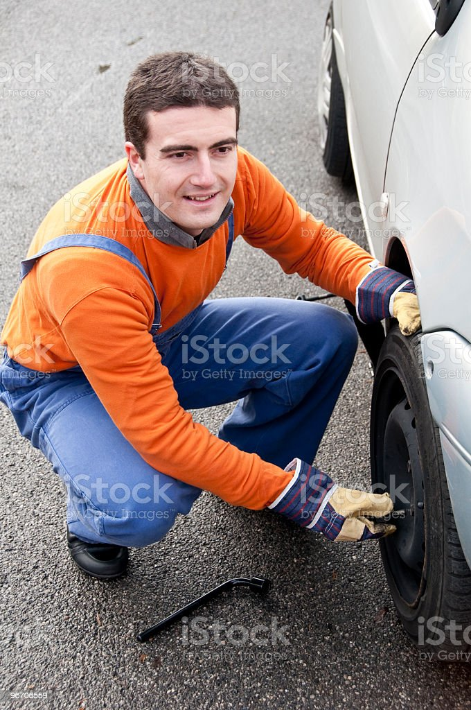Mechanic changing a tyre royalty-free stock photo