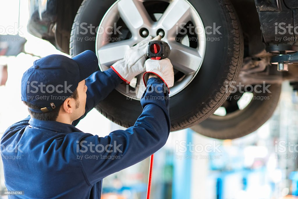 Mechanic changing a wheel on a car stock photo