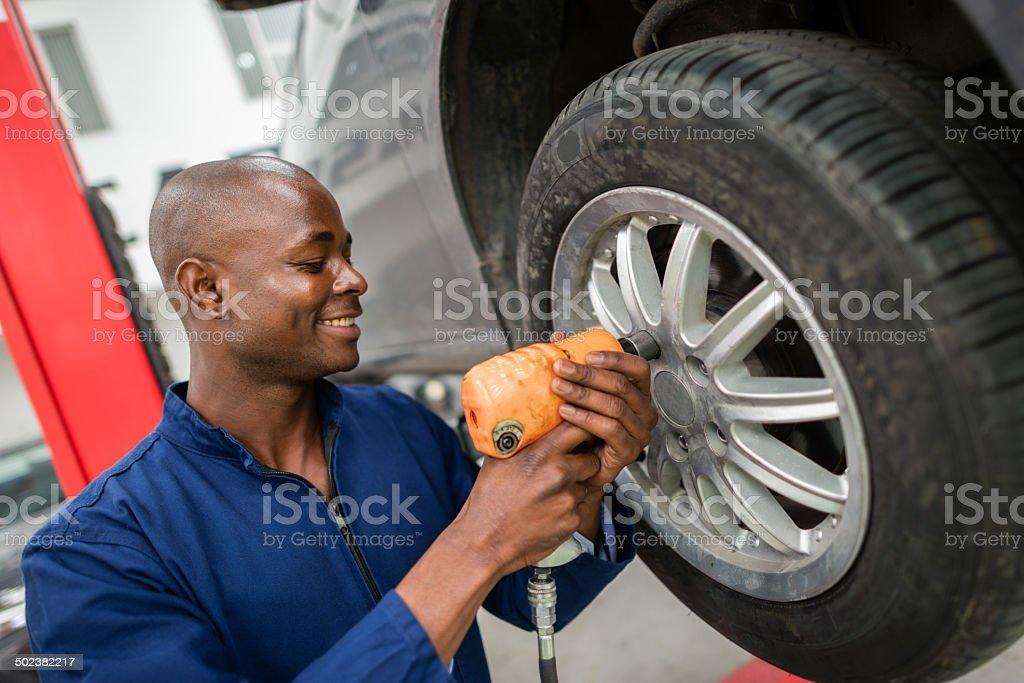 Mechanic changing a wheel stock photo