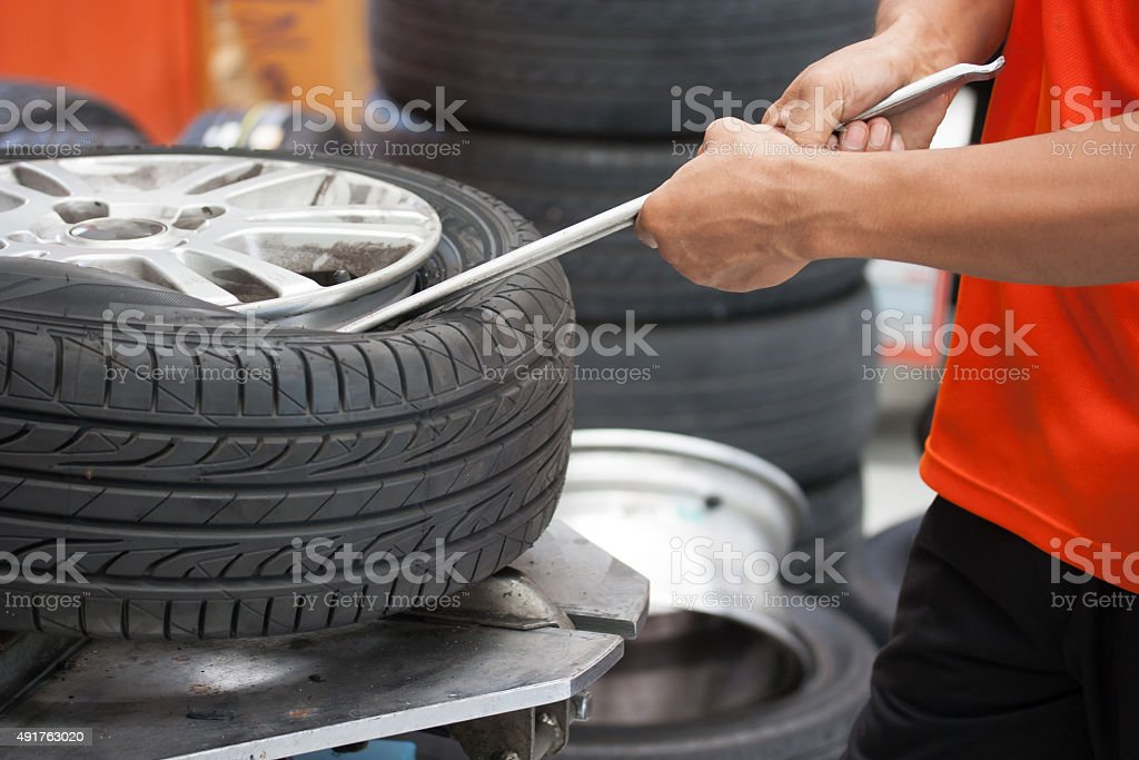 Mechanic changing car tire closeup stock photo