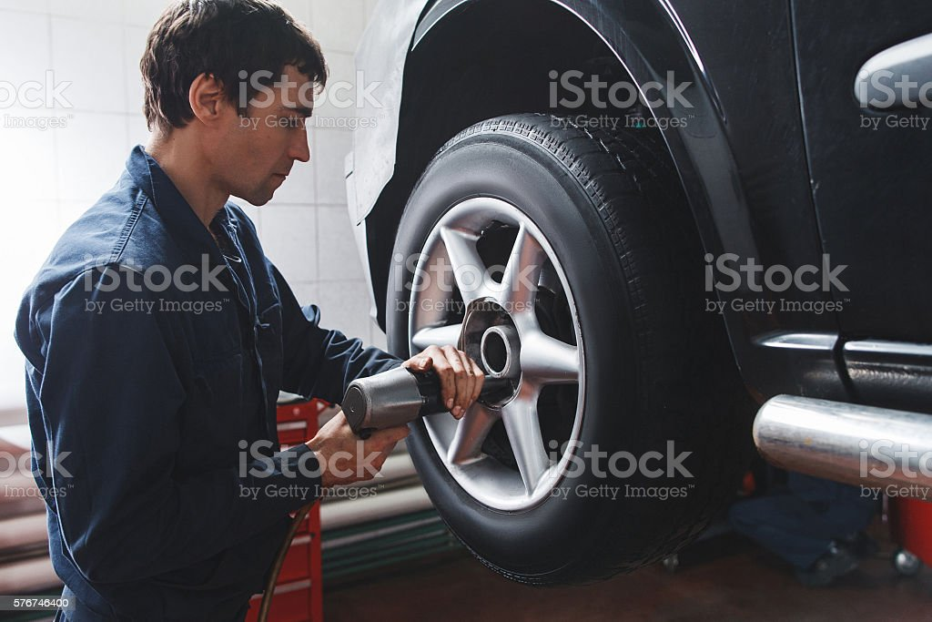 Mechanic changing car wheel in auto repair shop stock photo