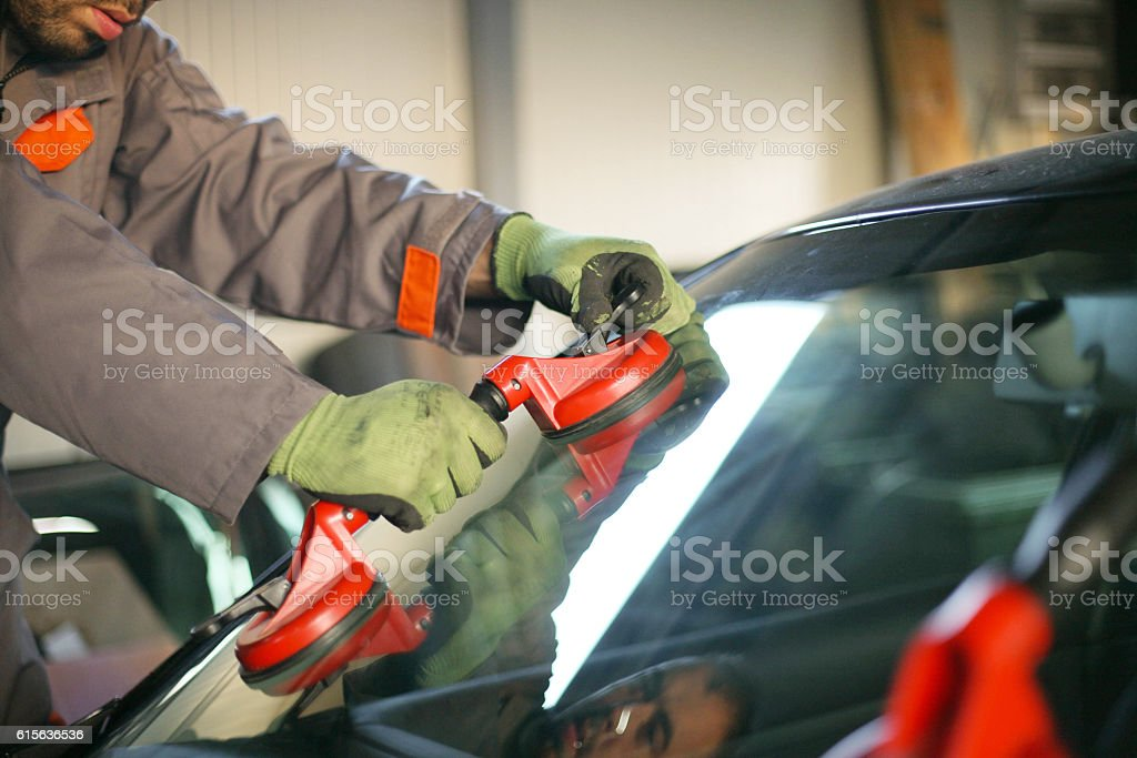 Mechanic changing glass on car. stock photo