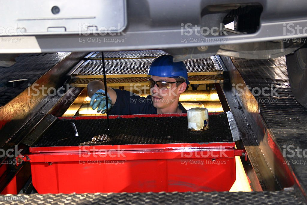Mechanic changing oil under a car stock photo