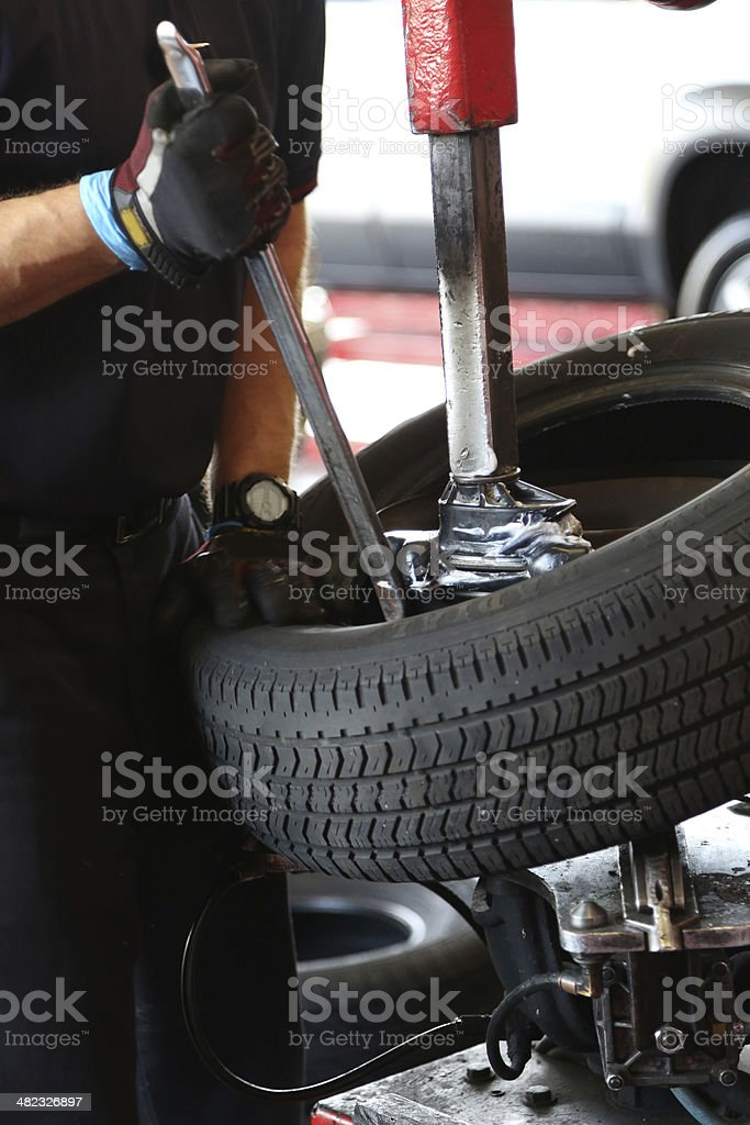 Mechanic changing tire in auto shop stock photo