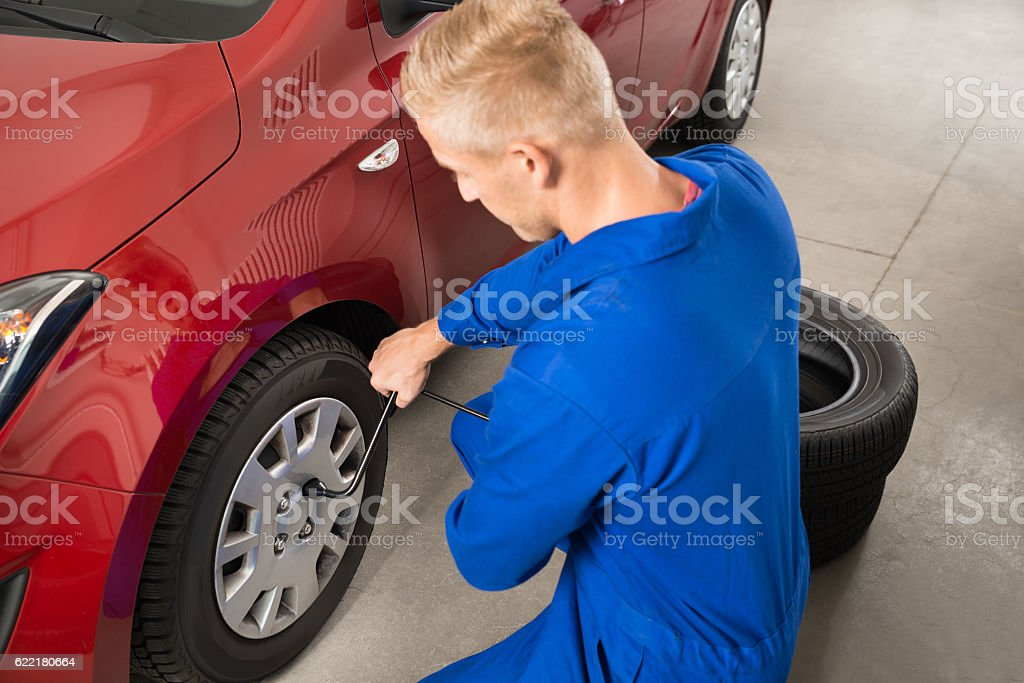 Mechanic Changing Tire In Garage stock photo