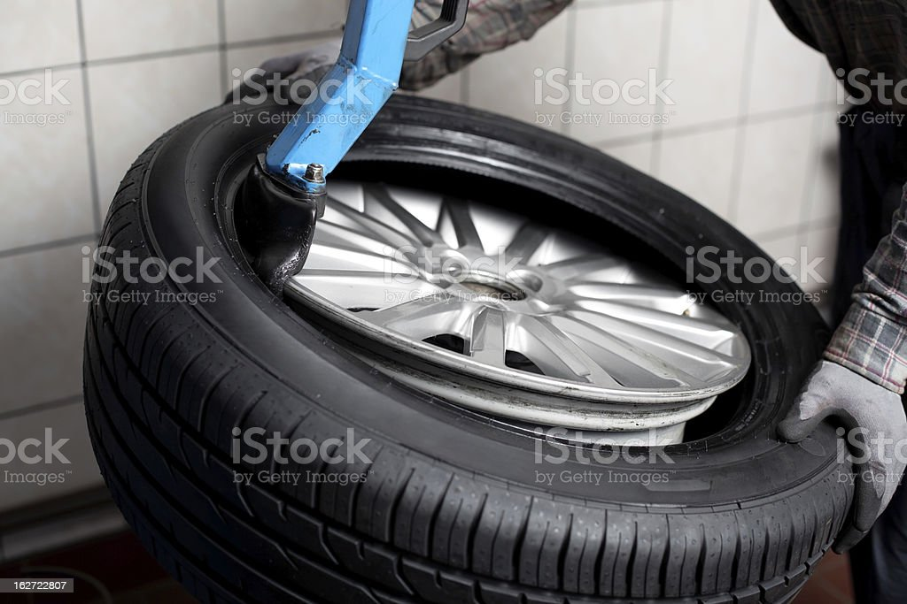 Mechanic changing tyre royalty-free stock photo