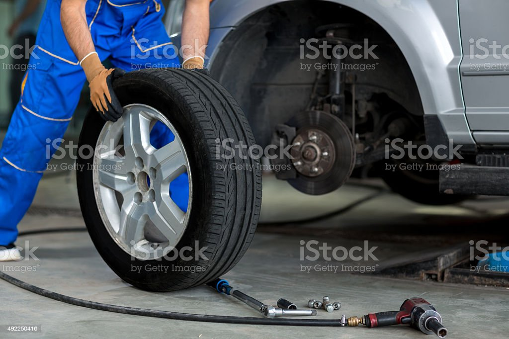 mechanic changing wheel of a modern car stock photo